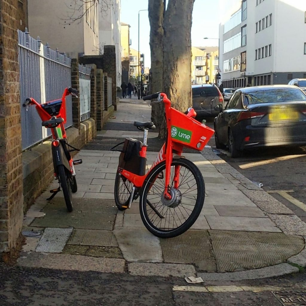 Lime hire bikes on the pavement.